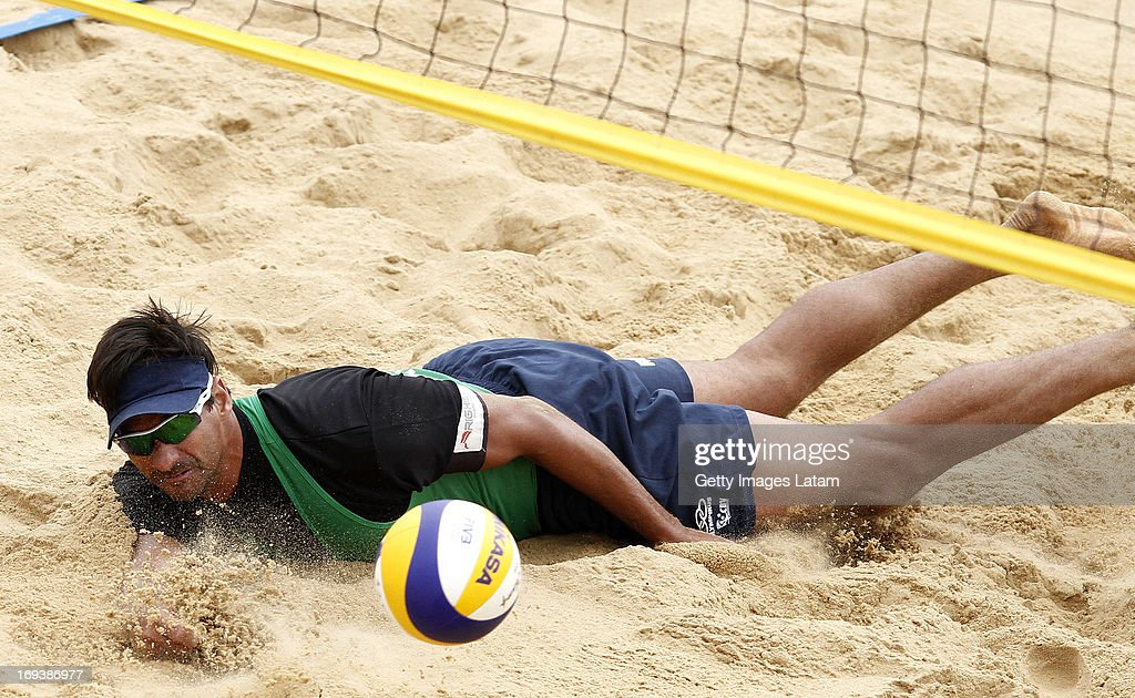 Ricardo Santos (in green) of Brazil dives for the ball during a match against Brazil as part of day two of Corrientes Grand Slam of FIVB World Tour at Arazaty Beach on May 23, 2013 in Corrientes, Argentina.