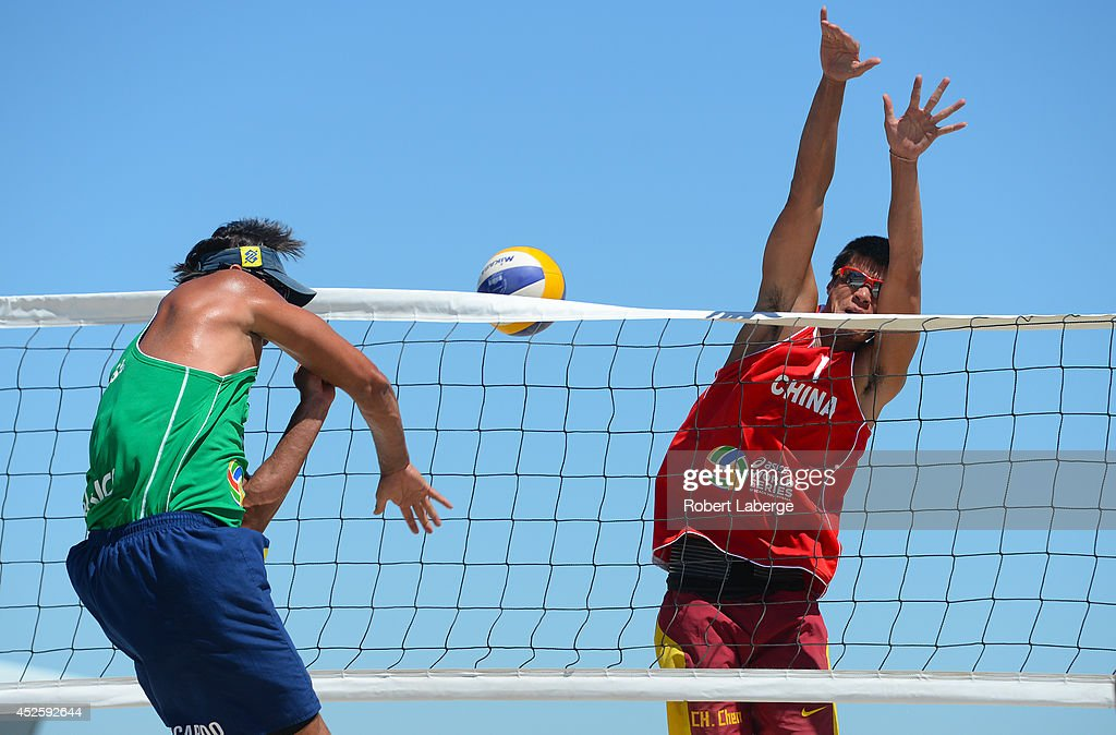 Ricardo Santos of Brazil (left) spikes the ball against Cheng Cheng of China during the FIVB Long Beach Grand Slam on July 23, 2014 in Long Beach, California.