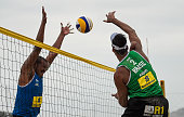 Ricardo Santos of Brazil spikes the ball as Lipe Rodrigues of Brazil attempts a block during the FIVB Beach Volleyball World Tour Rio Open at...