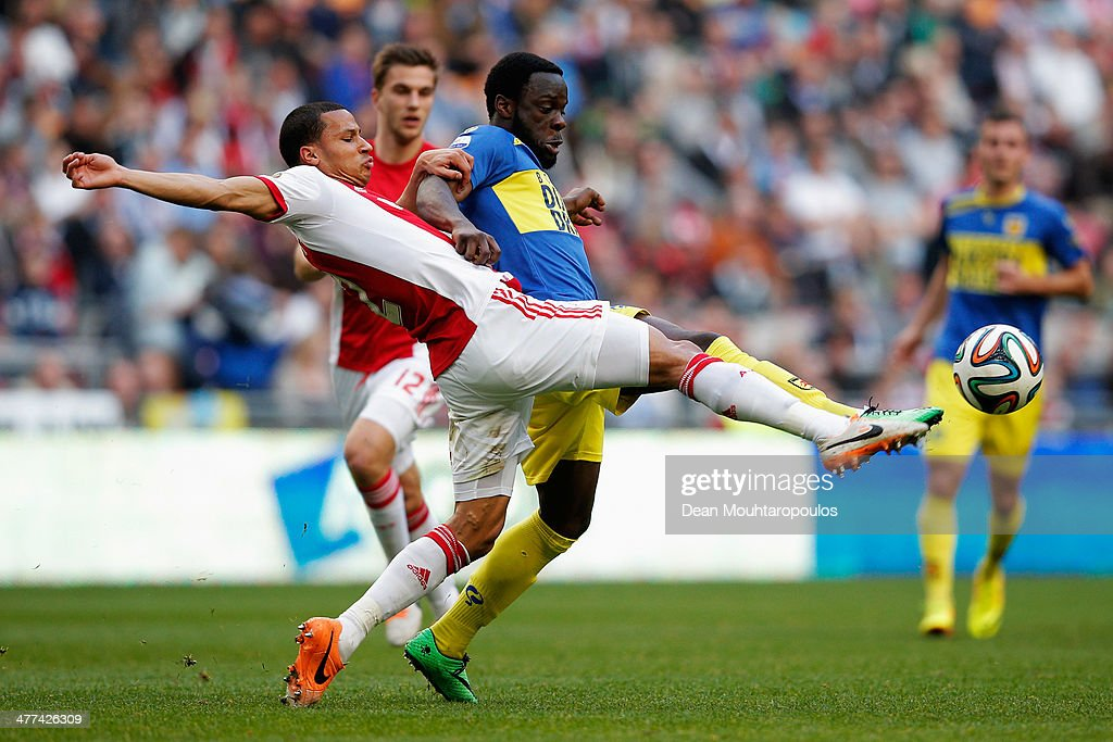 Ricardo Van Rhijn of Ajax tackles Elvis Manu of Cambuur during the Eredivisie match between Ajax Amsterdam and SC Cambuur Leeuwarden at Amsterdam Arena on March 9, 2014 in Amsterdam, Netherlands.