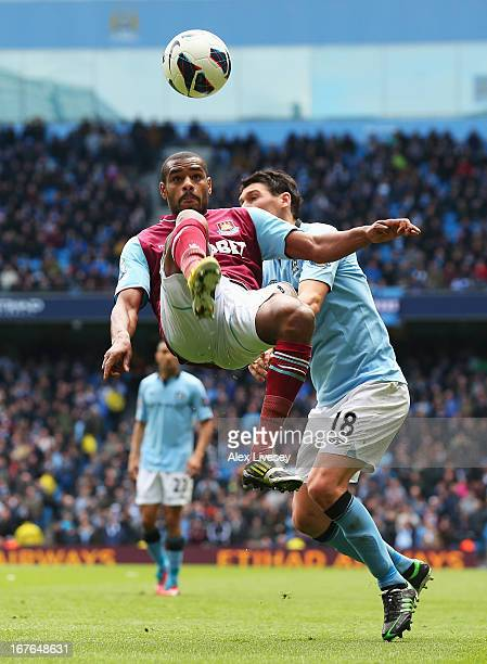 Ricardo Vaz Te of West Ham United makes a clearance under pressure from Gareth Barry of Manchester City during the Barclays Premier League match...