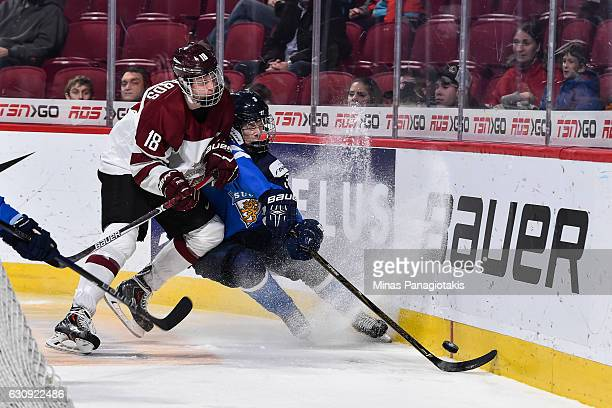 Ricards Bernhards of Team Latvia forces Urho Vaakanainen of Team Finland into the boards during the 2017 IIHF World Junior Championship relegation...