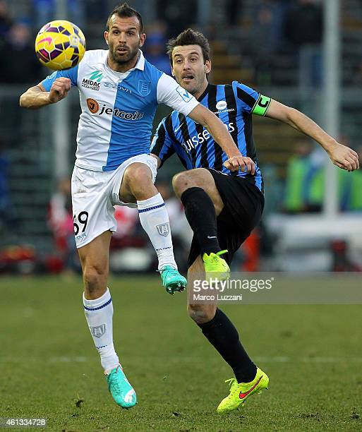 Riccardo Meggiorini of AC Chievo Verona competes for the ball with Gianpaolo Bellini of Atalanta BC during the Serie A match between Atalanta BC and...