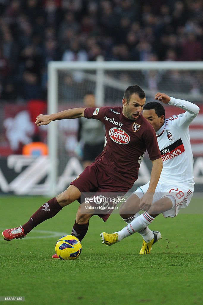 Riccardo Meggiorini (L) of Torino FC in action against Urby Emanuelson of AC Milan during the Serie A match between Torino FC and AC Milan at Stadio Olimpico di Torino on December 9, 2012 in Turin, Italy.