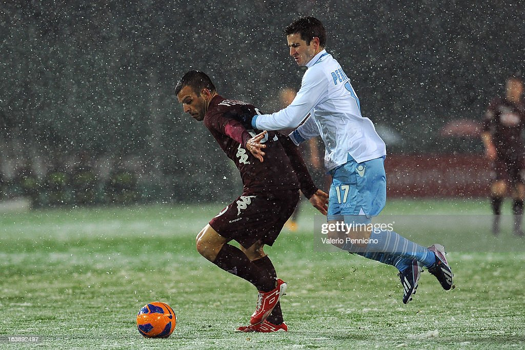 Riccardo Meggiorini (L) of Torino FC is challenged by Bruno Pereirinha of S.S. Lazio during the Serie A match between Torino FC and S.S. Lazio at Stadio Olimpico di Torino on March 17, 2013 in Turin, Italy.
