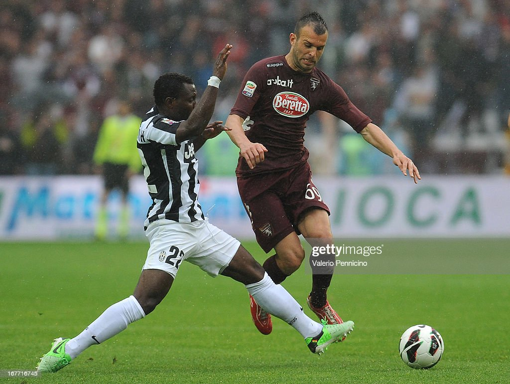 Riccardo Meggiorini (R) of Torino FC is challenged by Kwadwo Asamoah of Juventus during the Serie A match between Torino FC and Juventus at Stadio Olimpico di Torino on April 28, 2013 in Turin, Italy.