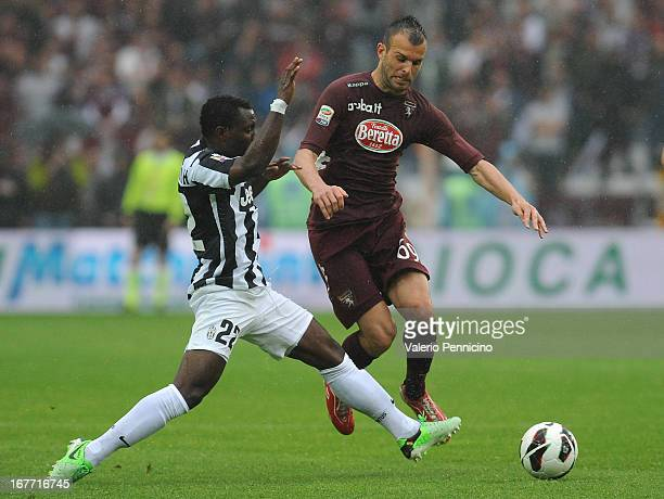 Riccardo Meggiorini of Torino FC is challenged by Kwadwo Asamoah of Juventus during the Serie A match between Torino FC and Juventus at Stadio...