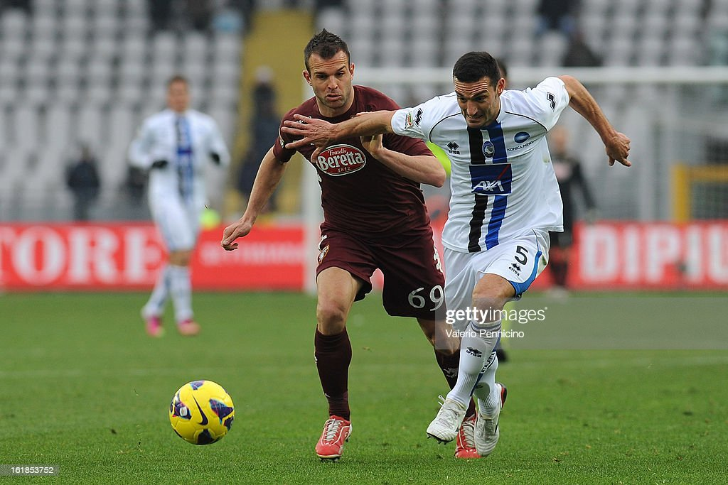Riccardo Meggiorini (L) of Torino FC is challenged by Lionel Scaloni of Atalanta BC during the Serie A match between Torino FC and Atalanta BC at Stadio Olimpico di Torino on February 17, 2013 in Turin, Italy.