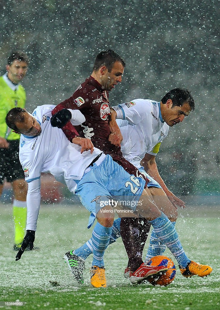 Riccardo Meggiorini (C) of Torino FC is challenged by Stefan Daniel Radu (L) and Cristian Ledesma of S.S. Lazio during the Serie A match between Torino FC and S.S. Lazio at Stadio Olimpico di Torino on March 17, 2013 in Turin, Italy.