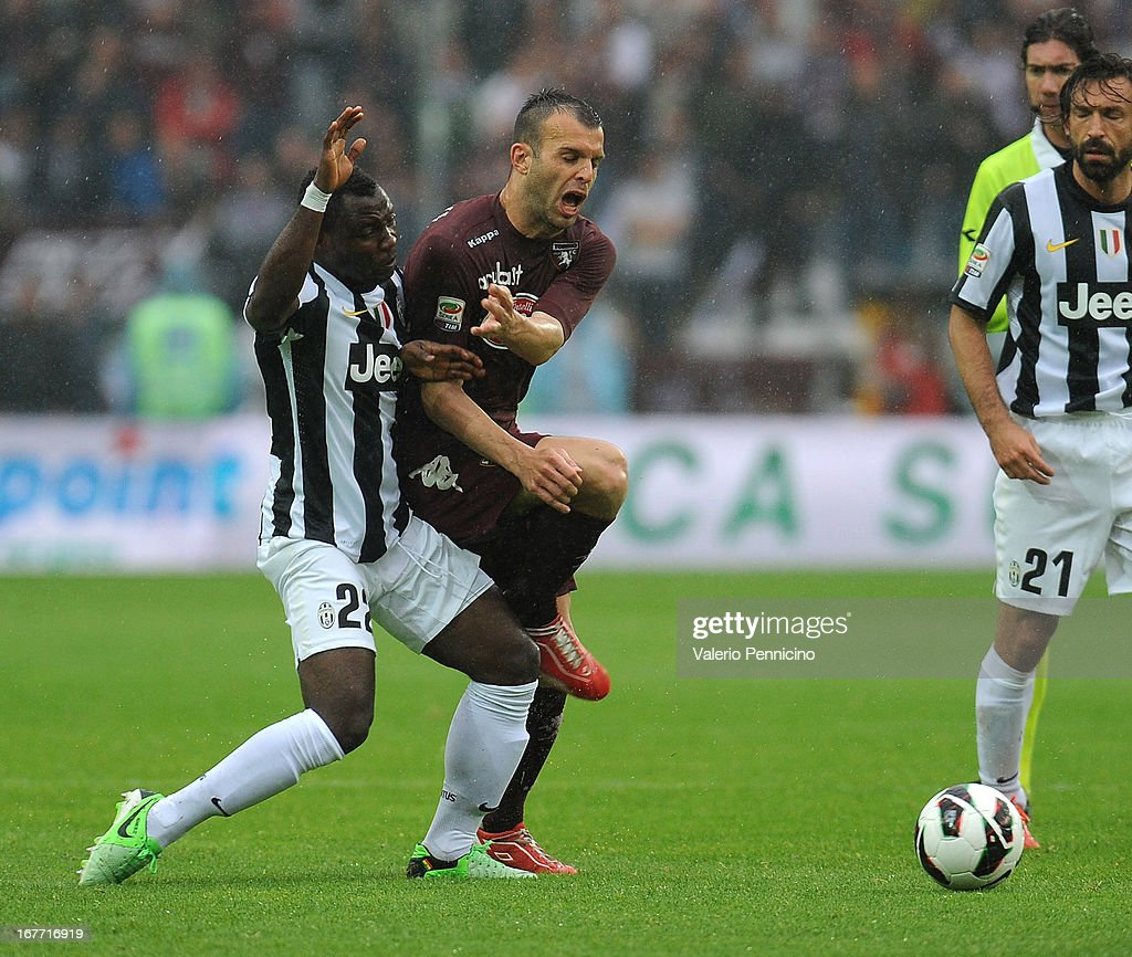 Riccardo Meggiorini (R) of Torino FC is tackled by Kwadwo Asamoah of Juventus during the Serie A match between Torino FC and Juventus at Stadio Olimpico di Torino on April 28, 2013 in Turin, Italy.