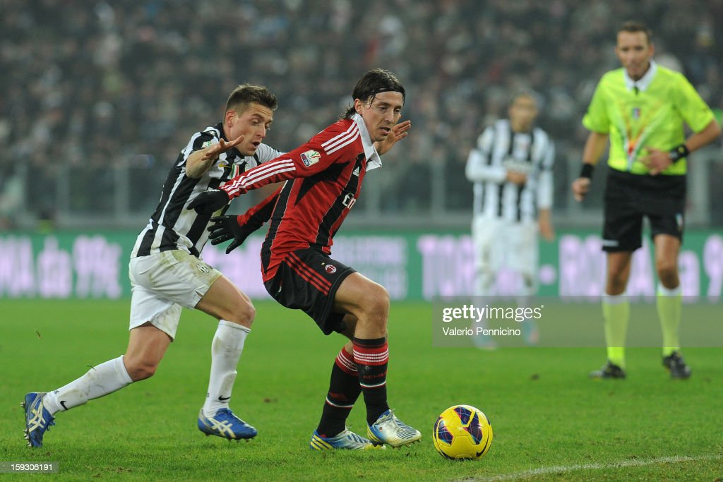 Riccardo Montolivo (R) of AC Milan in action against Emanuele Giaccherini of Juventus FC during the TIM cup match between Juventus FC and AC Milan at Juventus Arena on January 9, 2013 in Turin, Italy.