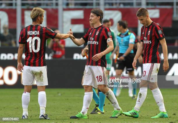 Riccardo Montolivo of AC Milan shakes hands with his team mates Keisuke Honda at the end of the Serie A match between AC Milan and Bologna FC at...