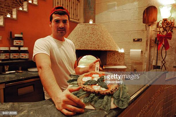 Riccardo Rinaldo a pizzaiolo poses with a pie of traditional Margherita pizza at Zero Otto Nove an Italian pizzeria located at 2357 Arthur Avenue in...