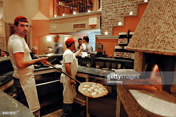 Riccardo Rinaldo a pizzaiolo pulls a pie of traditional Margherita pizza out of a woodburning pizza oven at Zero Otto Nove an Italian pizzeria...