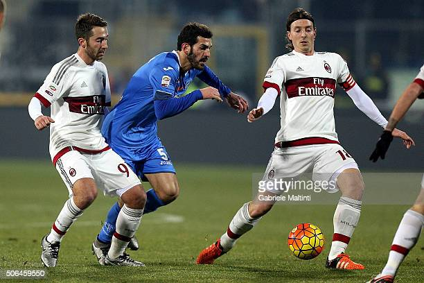 Riccardo Saponara of Empoli FC battles for the ball with Andrea Bertolacci and Riccardo Momntolivo of AC Milan during the Serie A match between...