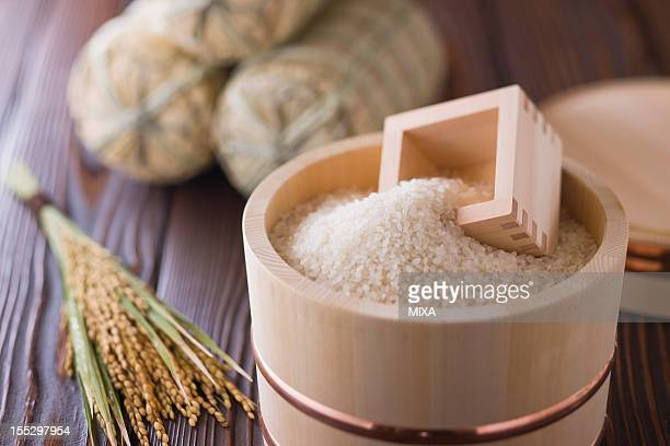 Rice and Measuring Cup in Wooden Tub