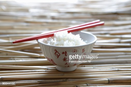 Rice in Asian bowl with chopsticks, close up : Stock Photo