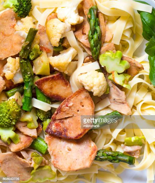 Rice noodles rolled on a fork. Grilled chicken kebab with vegetables and pasta