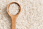 Rice on a wooden spoon. Close up, top view, high resolution product.