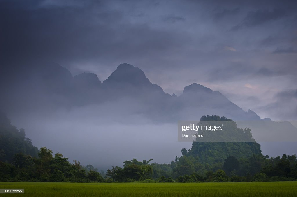 Rice paddies and mountains covered in vegetation in mist and clouds.  Vang Vieng, Laos, Asia.