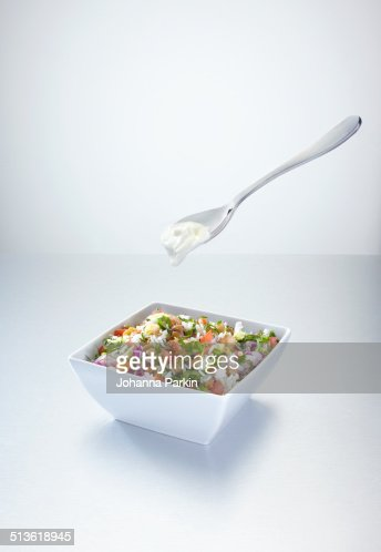 Rice salad with yoghurt on a floating spoon