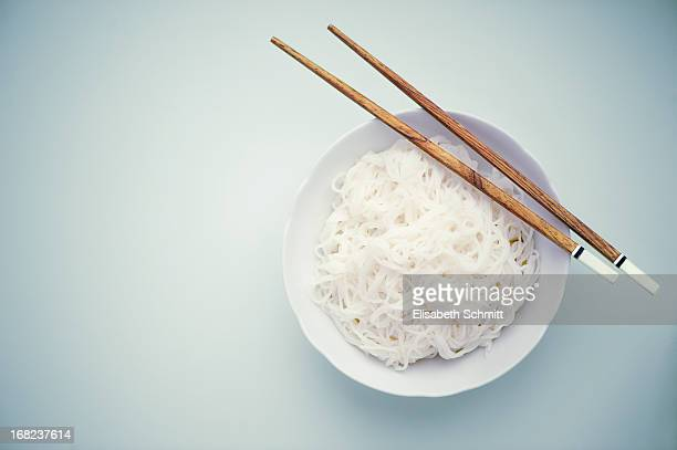 Rice vermicelli in bowl and chopsticks