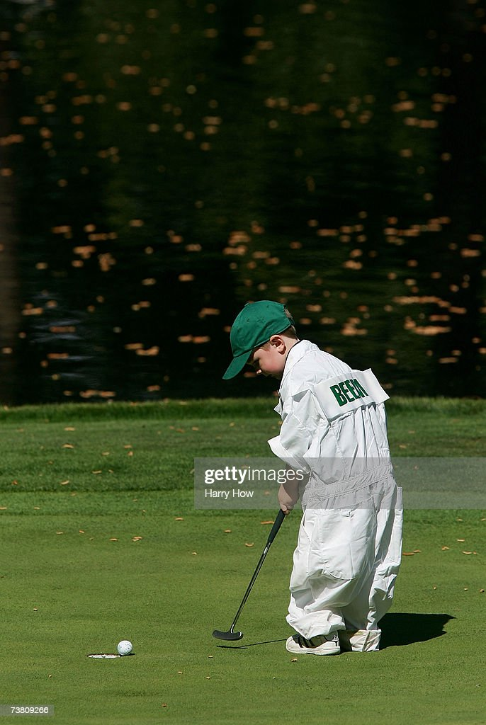 Rich Beem's son Michael putts across the ninth green during the Par3 contest prior to the start of The Masters at the Augusta National Golf Club on...