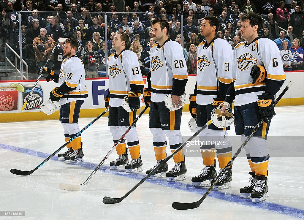 Rich Clune #16, Nick Spaling #13, Paul Gaustad #28, Seth Jones #3 and Shea Weber #6 of the Nashville Predators stand on the ice during the singing of the national anthems prior to puck drop against the Winnipeg Jets at the MTS Centre on November 8, 2013 in Winnipeg, Manitoba, Canada.