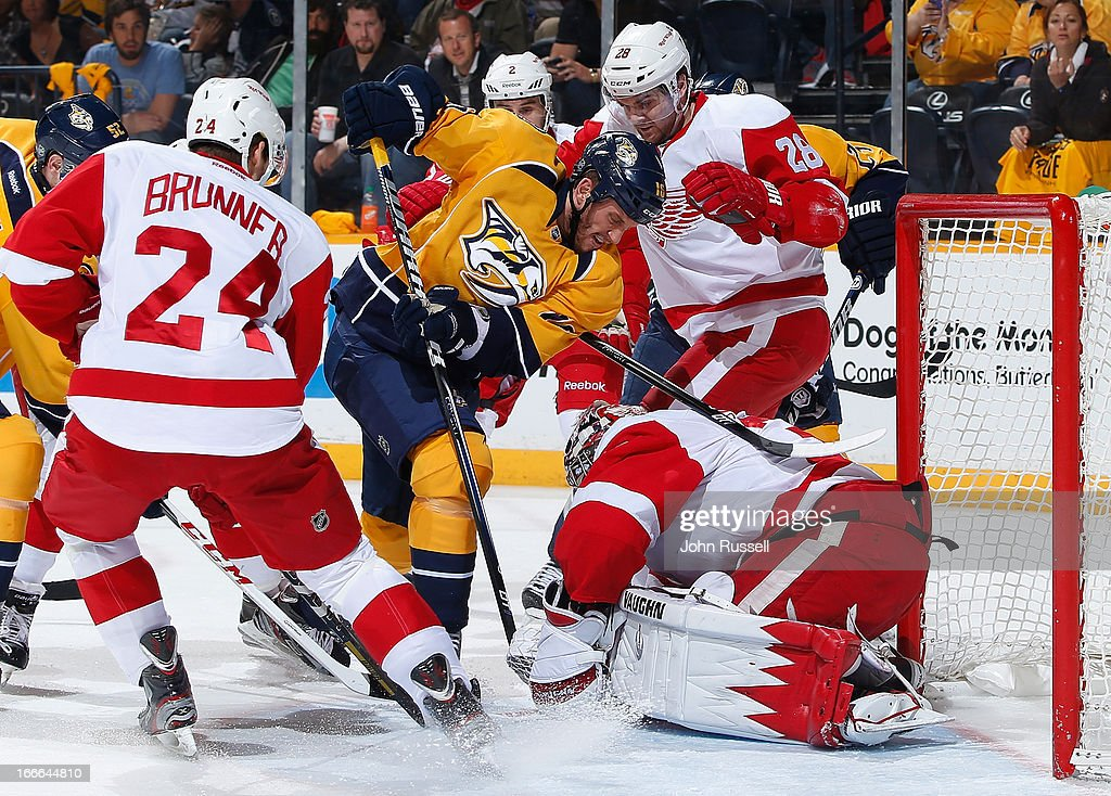 Rich Clune #16 of the Nashville Predators battles in the crease against goalie Jimmy Howard #35 of the Detroit Red Wings during an NHL game at the Bridgestone Arena on April 14, 2013 in Nashville, Tennessee.