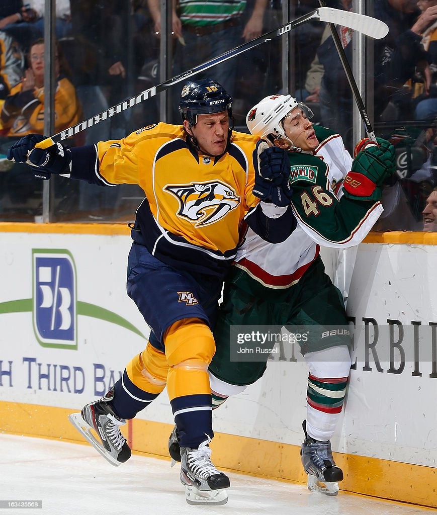 Rich Clune #16 of the Nashville Predators checks Jared Spurgeon #46 of the Minnesota Wild during an NHL game at the Bridgestone Arena on March 9, 2013 in Nashville, Tennessee.