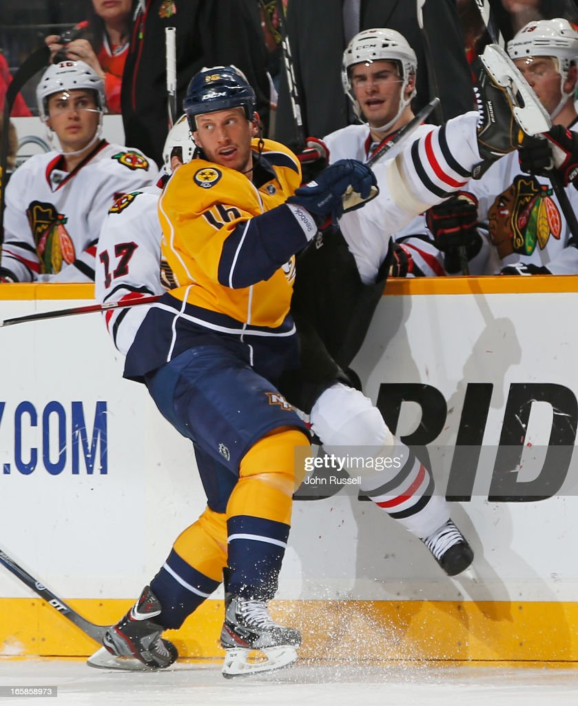 Rich Clune #16 of the Nashville Predators checks Sheldon Brookbank #17 of the Chicago Blackhawks during an NHL game at the Bridgestone Arena on April 6, 2013 in Nashville, Tennessee.