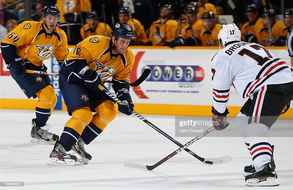 Rich Clune #16 of the Nashville Predators skates the puck into the zone against Sheldon Brookbank #17 of the Chicago Blackhawks during an NHL game at the Bridgestone Arena on April 6, 2013 in Nashville, Tennessee.