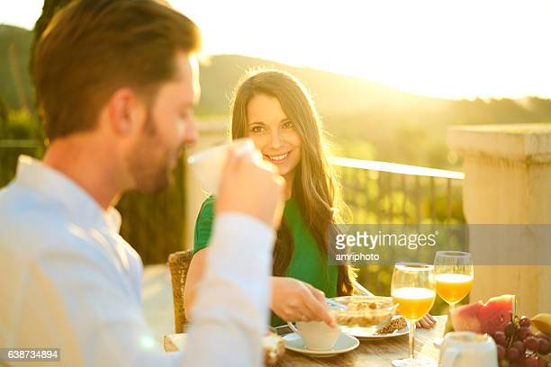 rich couple enjoying breakfast outside with sunshine