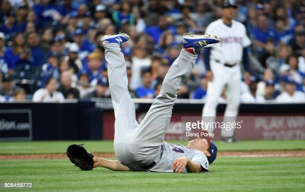 Rich Hill of the Los Angeles Dodgers falls on his back after throwing to first base during the second inning of a baseball game against the San Diego...