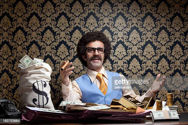 Rich man posing with money bags, gold bullions, dollar bills
