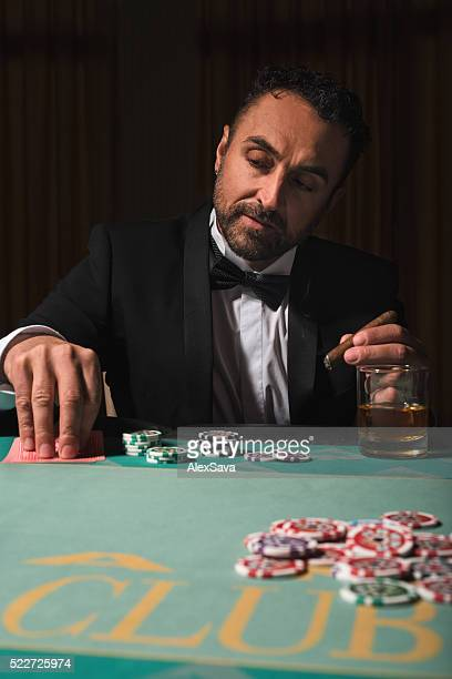 Rich mature man playing poker in a casino