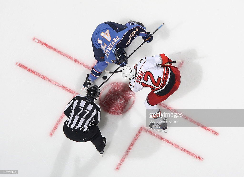 Rich Peverley of the Atlanta Thrashers wins a faceoff against Eric Staal of the Carolina Hurricanes at Philips Arena on March 7 2010 in Atlanta...