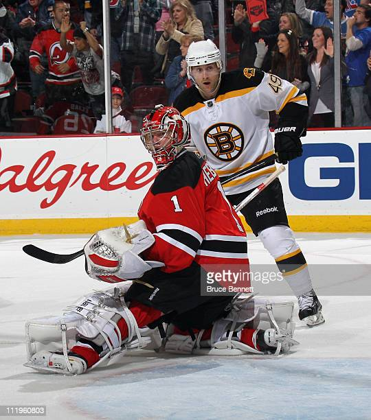 Rich Peverley of the Boston Bruins and Johan Hedberg of the New Jersey Devils watch a shot go wide of the net at the Prudential Center on April 10...