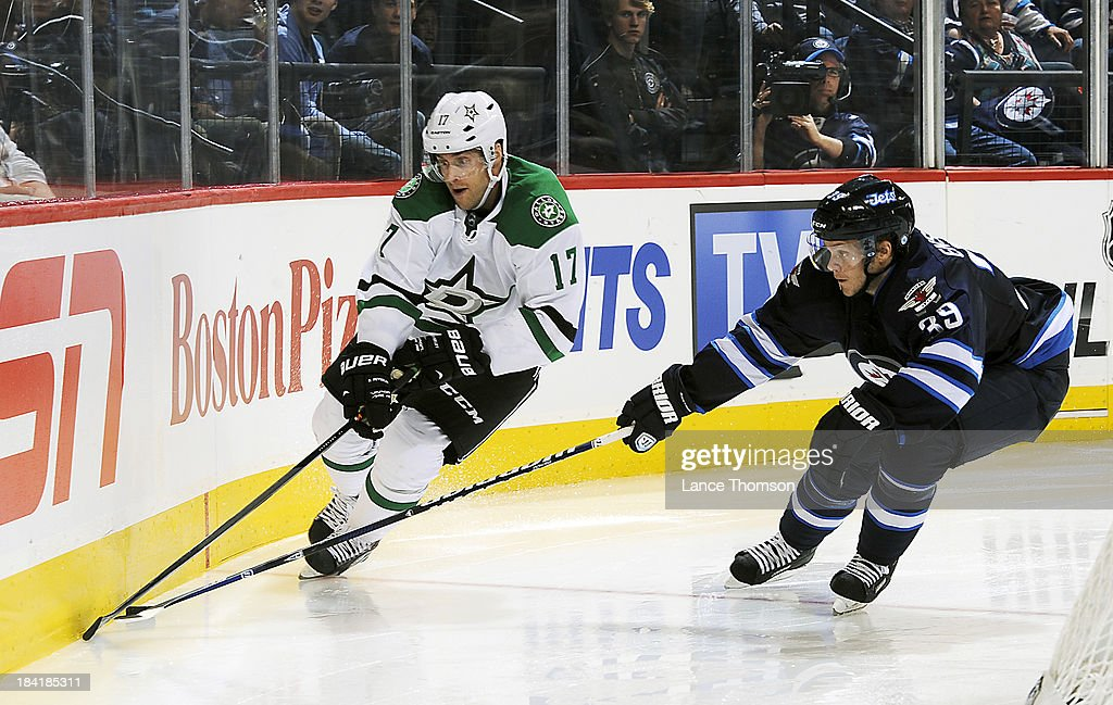 <a gi-track='captionPersonalityLinkClicked' href=/galleries/search?phrase=Rich+Peverley&family=editorial&specificpeople=554442 ng-click='$event.stopPropagation()'>Rich Peverley</a> #17 of the Dallas Stars battles <a gi-track='captionPersonalityLinkClicked' href=/galleries/search?phrase=Tobias+Enstrom&family=editorial&specificpeople=2538468 ng-click='$event.stopPropagation()'>Tobias Enstrom</a> #39 of the Winnipeg Jets for the puck along the boards during third period action at the MTS Centre on October 11, 2013 in Winnipeg, Manitoba, Canada.