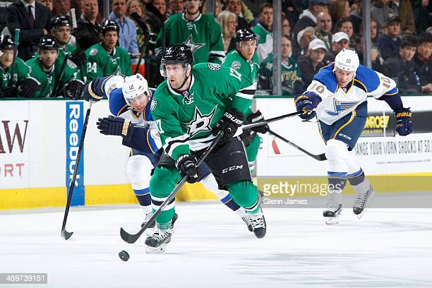 Rich Peverley of the Dallas Stars handles the puck ahead of Derek Roy of the St Louis Blues at the American Airlines Center on December 29 2013 in...