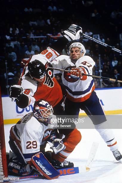 Rich Pilon of the New York Islanders crosschecks Eric Lindros of the Philadelphia Flyers into goalie Jamie McLennan of the Islanders circa 1995 at...