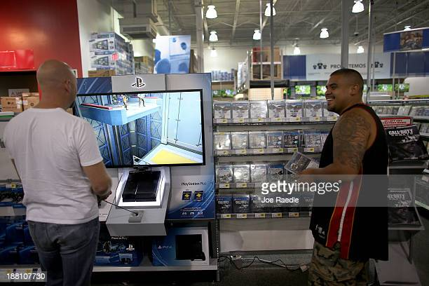 Rich Rhudy plays the new Sony Playstation 4 that is on display at Best Buy as George Arana buys games for his new Playstation 4 that he bought last...