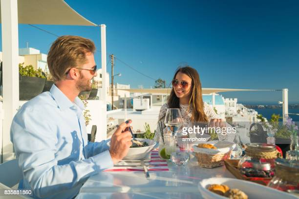 rich young couple having dinner in restaurant outdoors