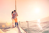 Rich young couple in love on sailboat cheering at sunset - Happy wander lifestyle concept sailing around world - Soft focus on rose quartz filter - Lens flare and tilted horizon as part of composition