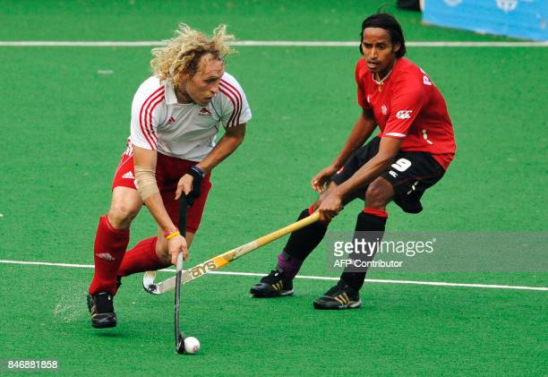 Richard Alexander of England fights for the ball with Keegan Pereira of Canada during their field hockey match at the Major Dhyan Chand National...