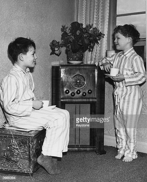 Richard and John Hutton sons of English cricketer Sir Leonard Hutton wearing pyjamas at home at Leeds They are listening to a broadcast of a test...