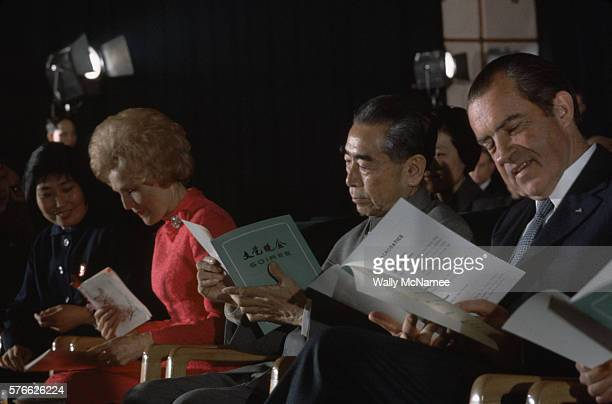 Richard and Pat Nixon sit on either side of Chinese Premier Chou EnLai looking at the programs for the soiree they are attending at the Great Hall of...