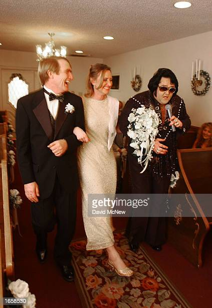 Richard and Suzanne Abraham are escorted by Elvis Presley impersonator Norm Jone down the aisle to renew their vows in celebration of their 25th...