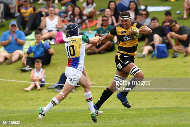 Richard Arnold of the Spirit fends off a tackle by Bryce Hegarty of the Rays during the round eight NRC match between Perth and the Sydney Rays at...