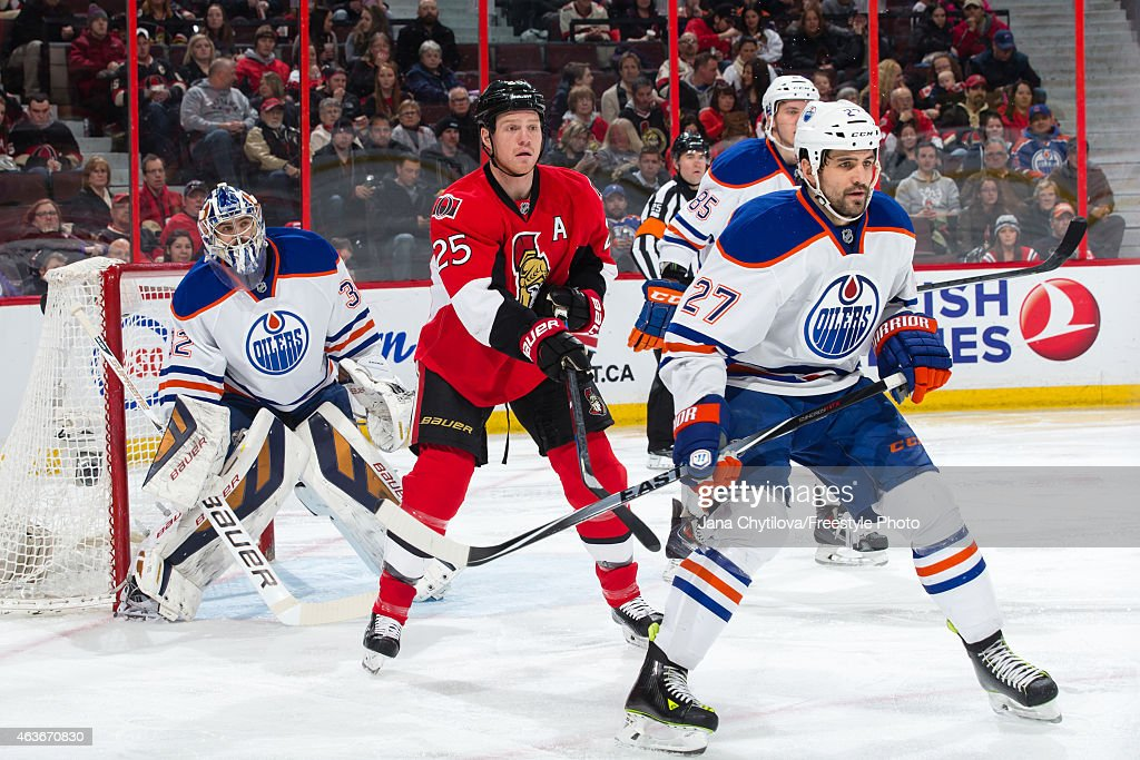 Richard Bachman and Boyd Gordon of the Edmonton Oilers defend against Chris Neil of the Ottawa Senators at Canadian Tire Centre on February 14 2015...